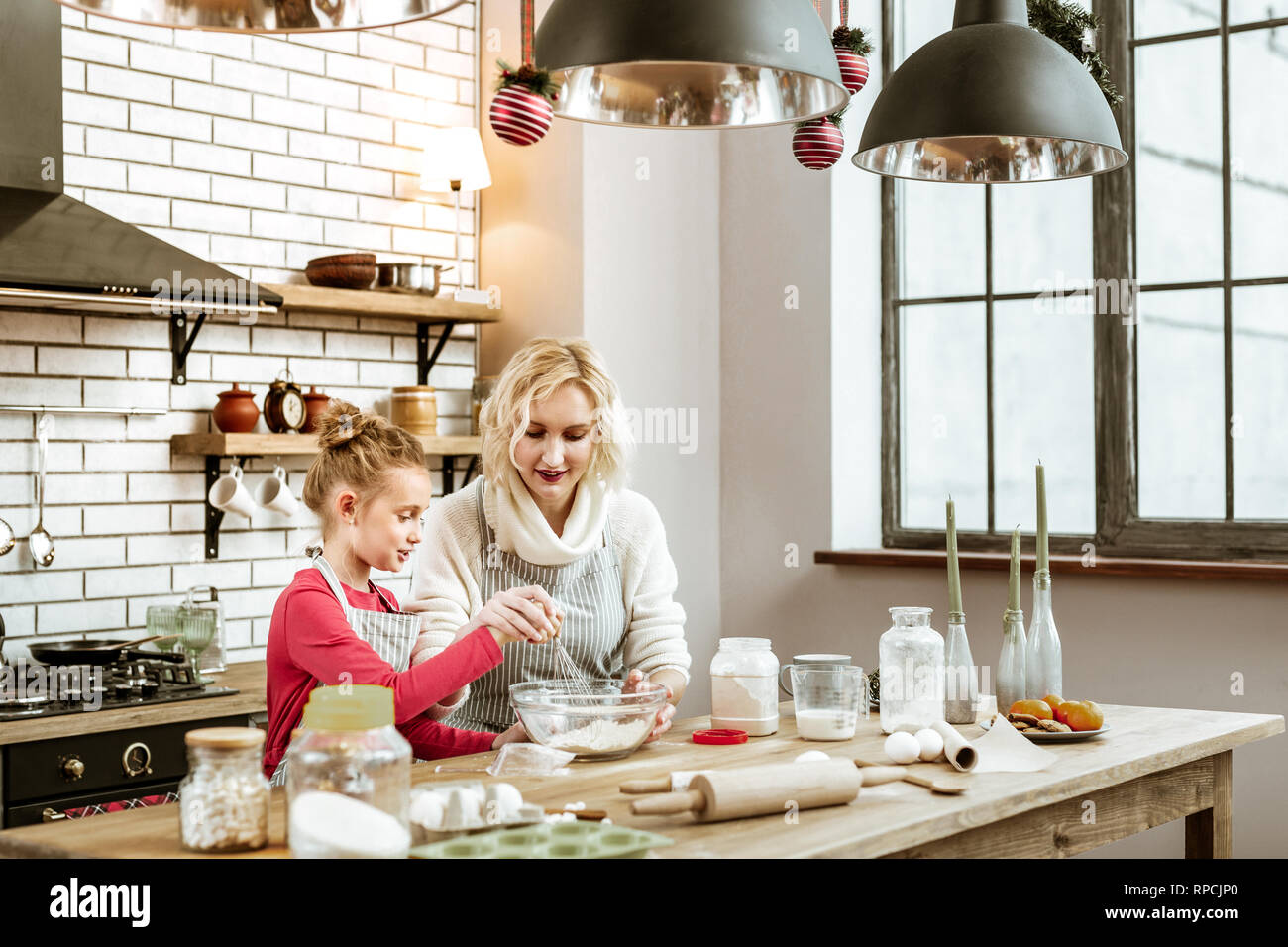 Pleasant short-haired mother spending time with daughter on furnished kitchen - Stock Image