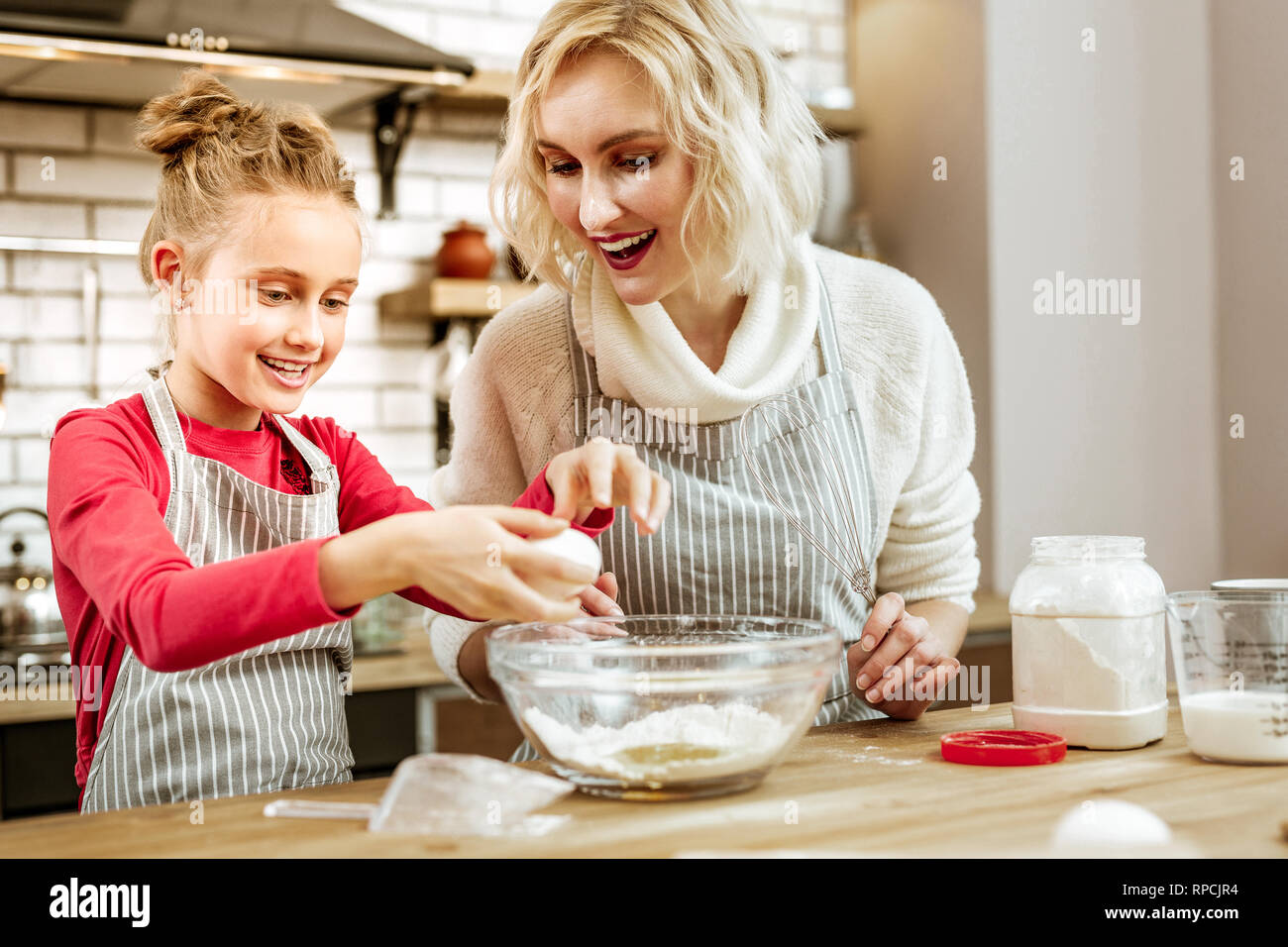 Smiling light-haired little child being entertained with cooking - Stock Image