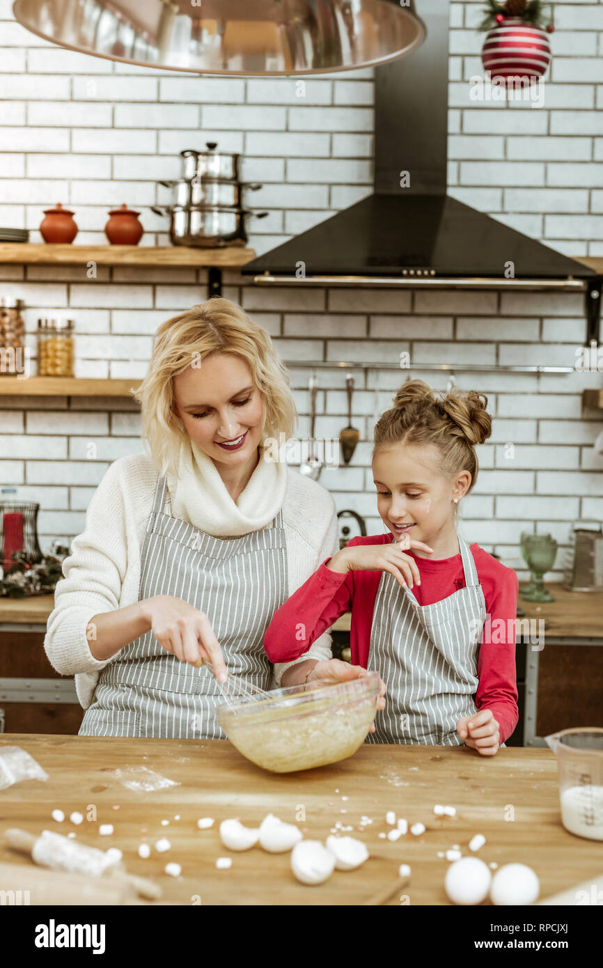 Cooking smiling mother and her curious daughter having mess on cooking table - Stock Image