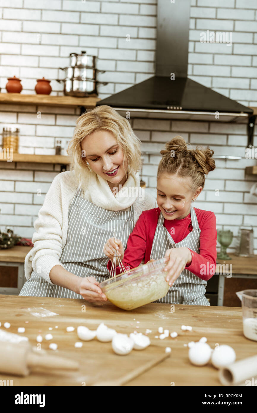 Attentive short-haired blonde lady guiding her daughter - Stock Image