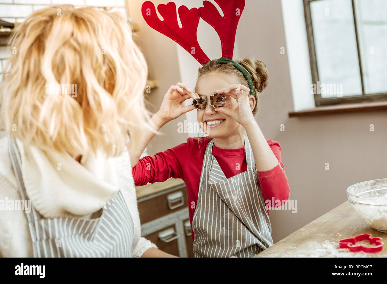 Little child with wide smile putting metal form for baking Stock Photo