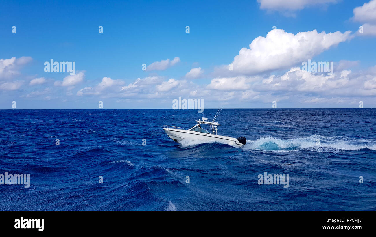 Speed fishing tender boat jumping the waves in the sea and cruising the blue ocean day in Bahamas. Blue beautiful water - Stock Image