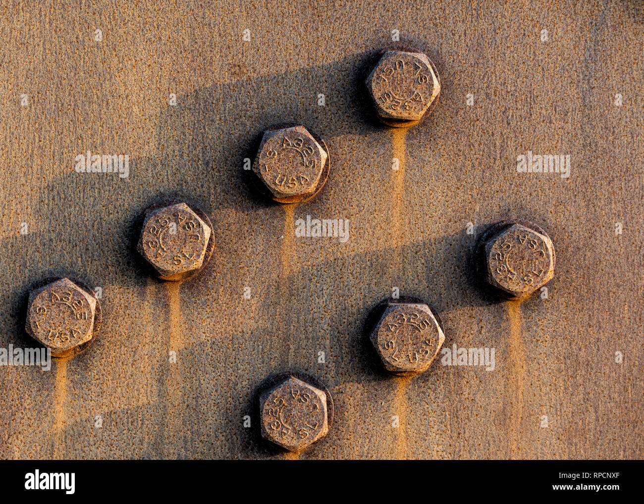 Groups of rusty weathered industrial strength bolts. - Stock Image