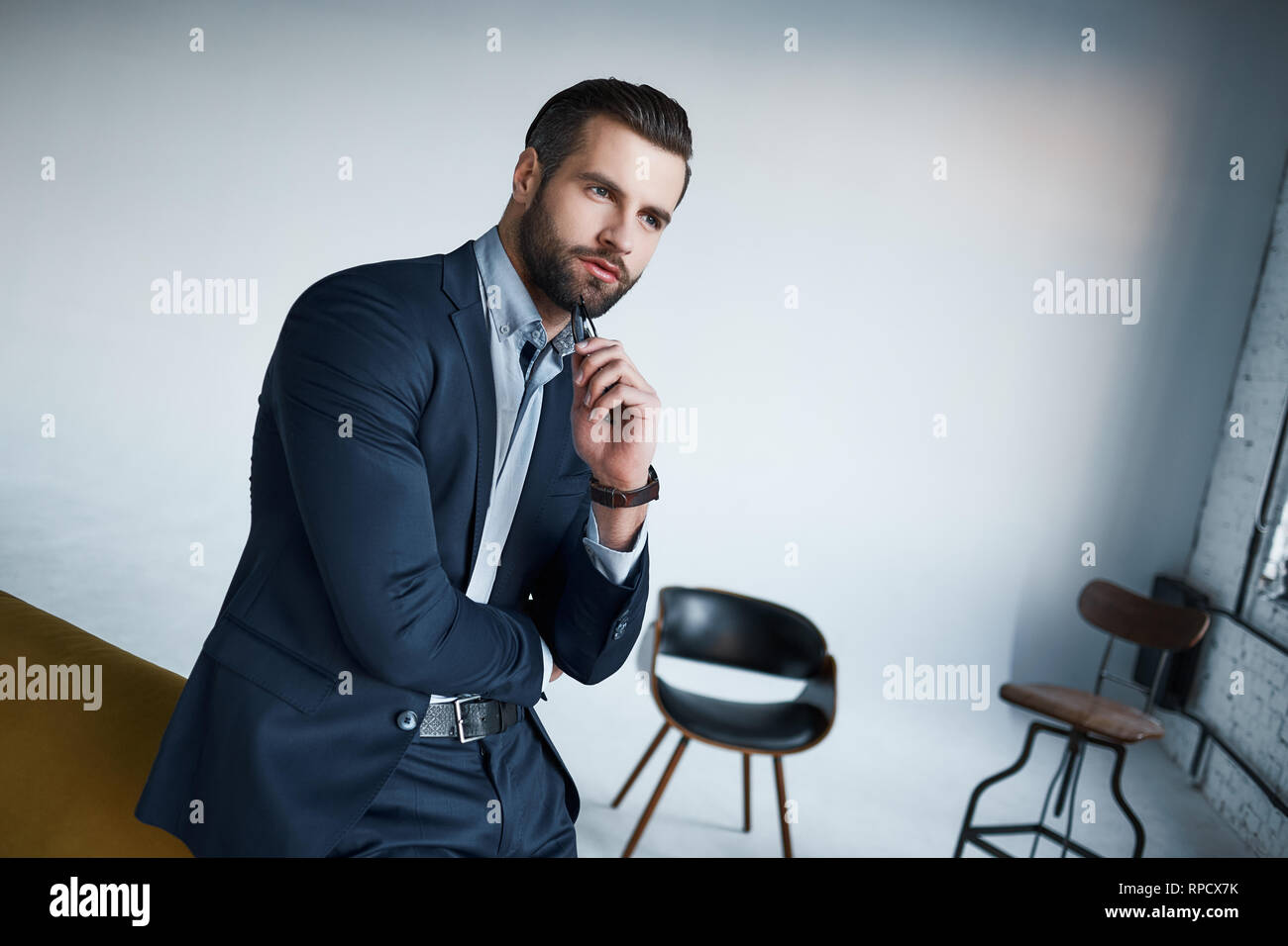Used to look perfect. Handsome young businessman is looking away while standing in his modern office. Bussiness look. Close-up portrait - Stock Image