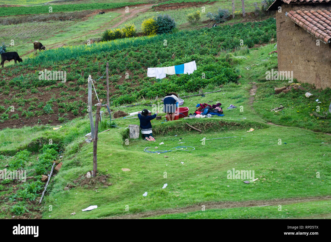 Cusco, Peru December 31th, 2018 : Mother and daughter washing clothes by hand, traditional customs of the city of Cusco in Peru - Stock Image
