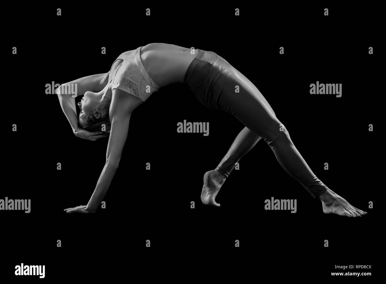 woman practicing yoga, 'wild thing' pose in the studio, black & white - Stock Image