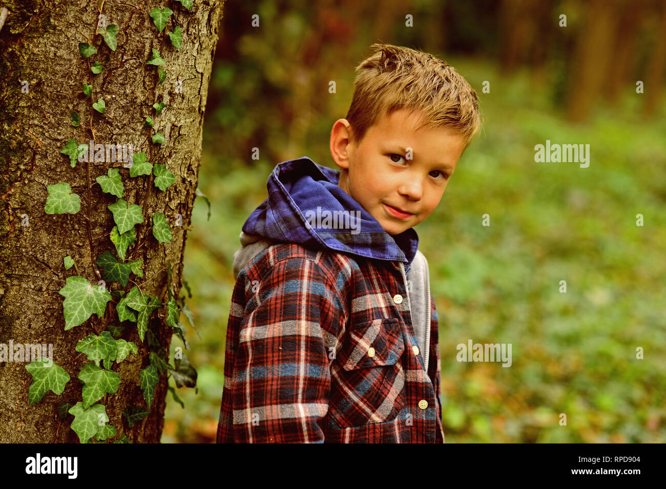Every single childhood matters. Small boy enjoy childhood years. Small boy play in forest. Childhood is a short season - Stock Image