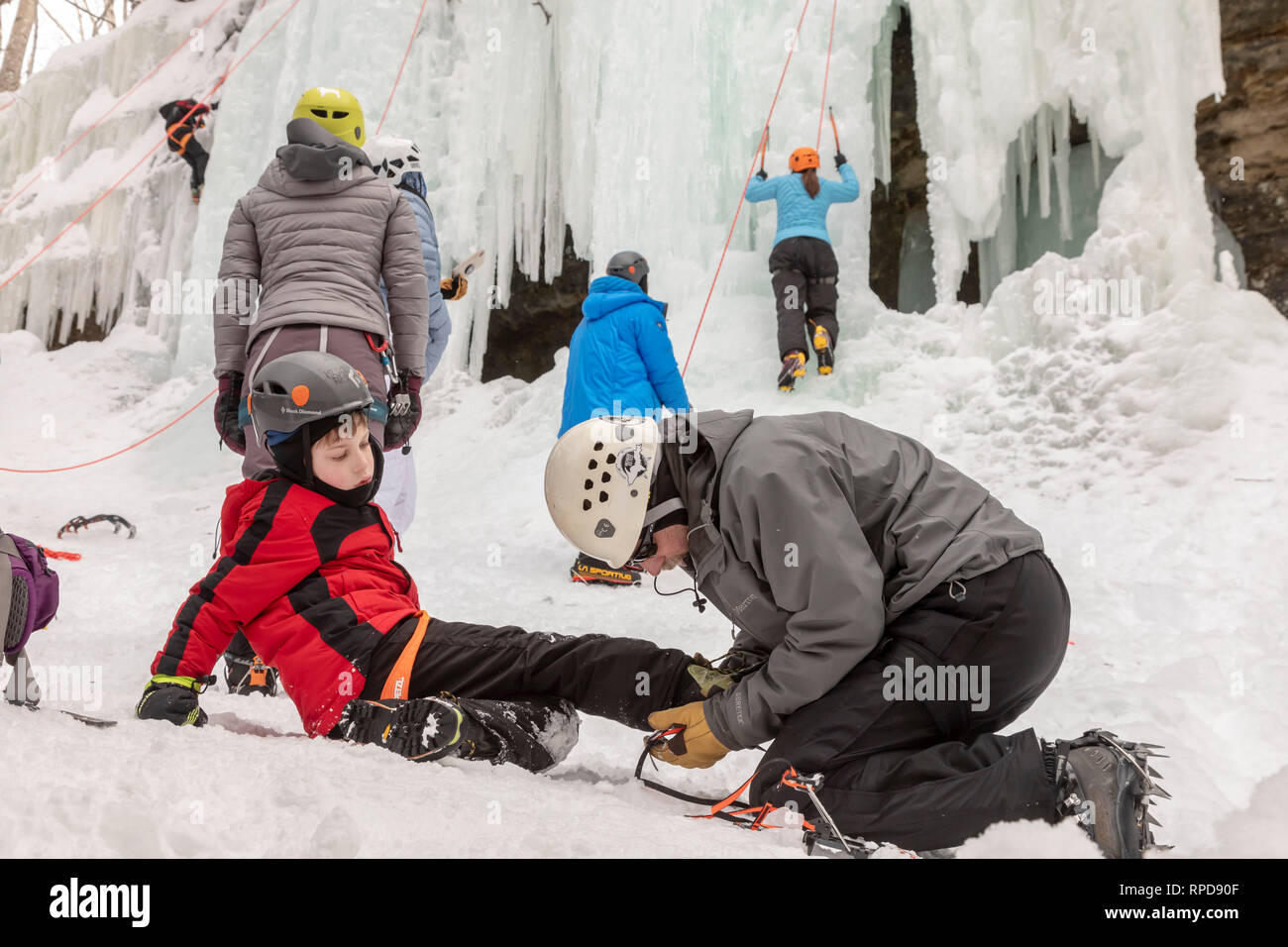 Munising, Michigan - A boy gets help in fitting crampons before climbing an ice wall during the annual Michigan Ice Fest. Participants climbed frozen  - Stock Image