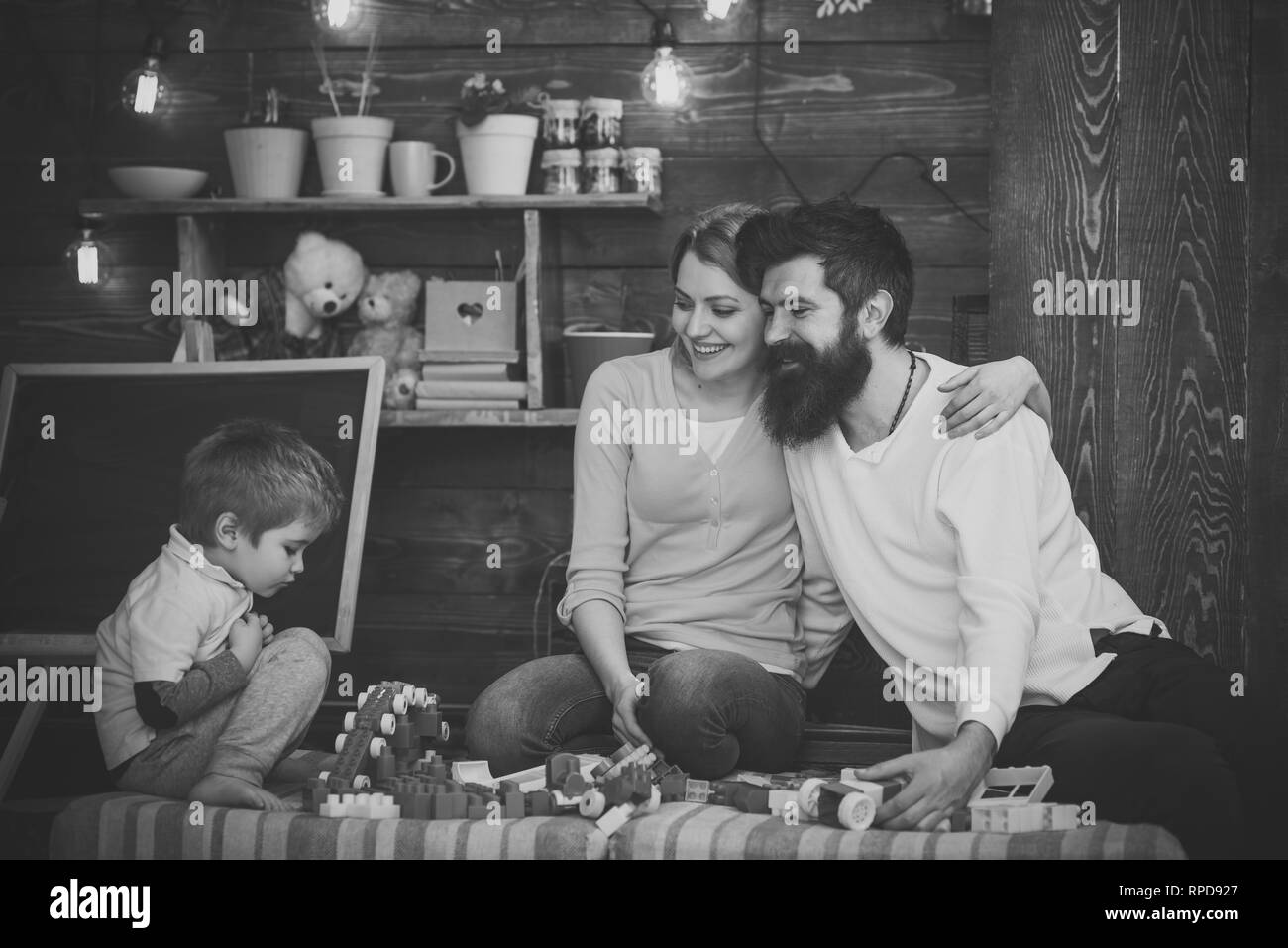 Happy parents hug each other while looking at son. Family playing with plastic blocks on sofa. Side view concentrated boy plays with toy train - Stock Image