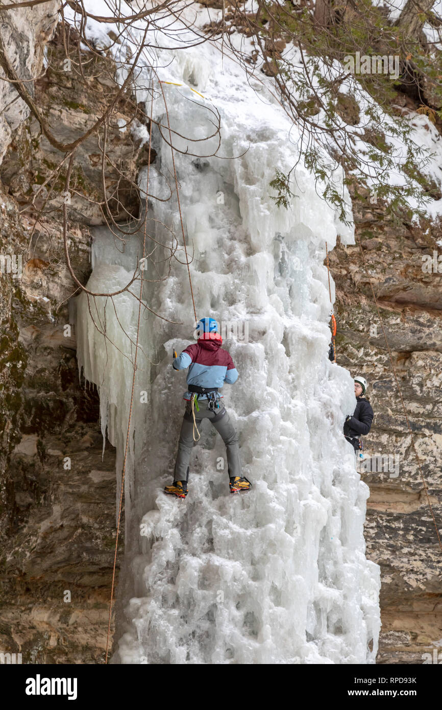 Munising, Michigan - Participants in the annual Michigan Ice Fest climb a frozen waterfall in Pictured Rocks National Lakeshore. - Stock Image