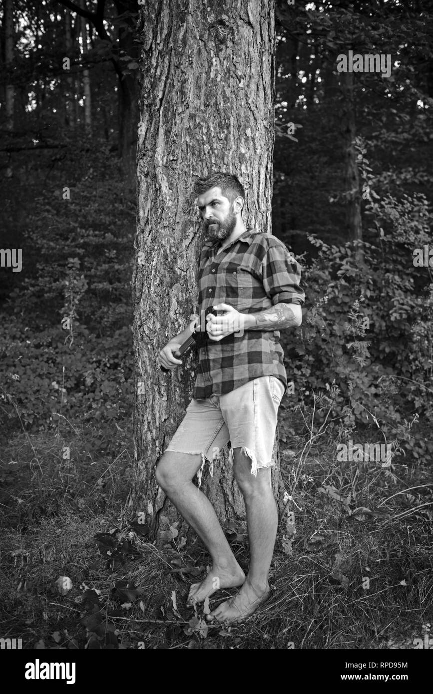 549a16d1 Traveler in plaid shirt and jean shorts travel barefoot. Bearded man with  shovel in forest