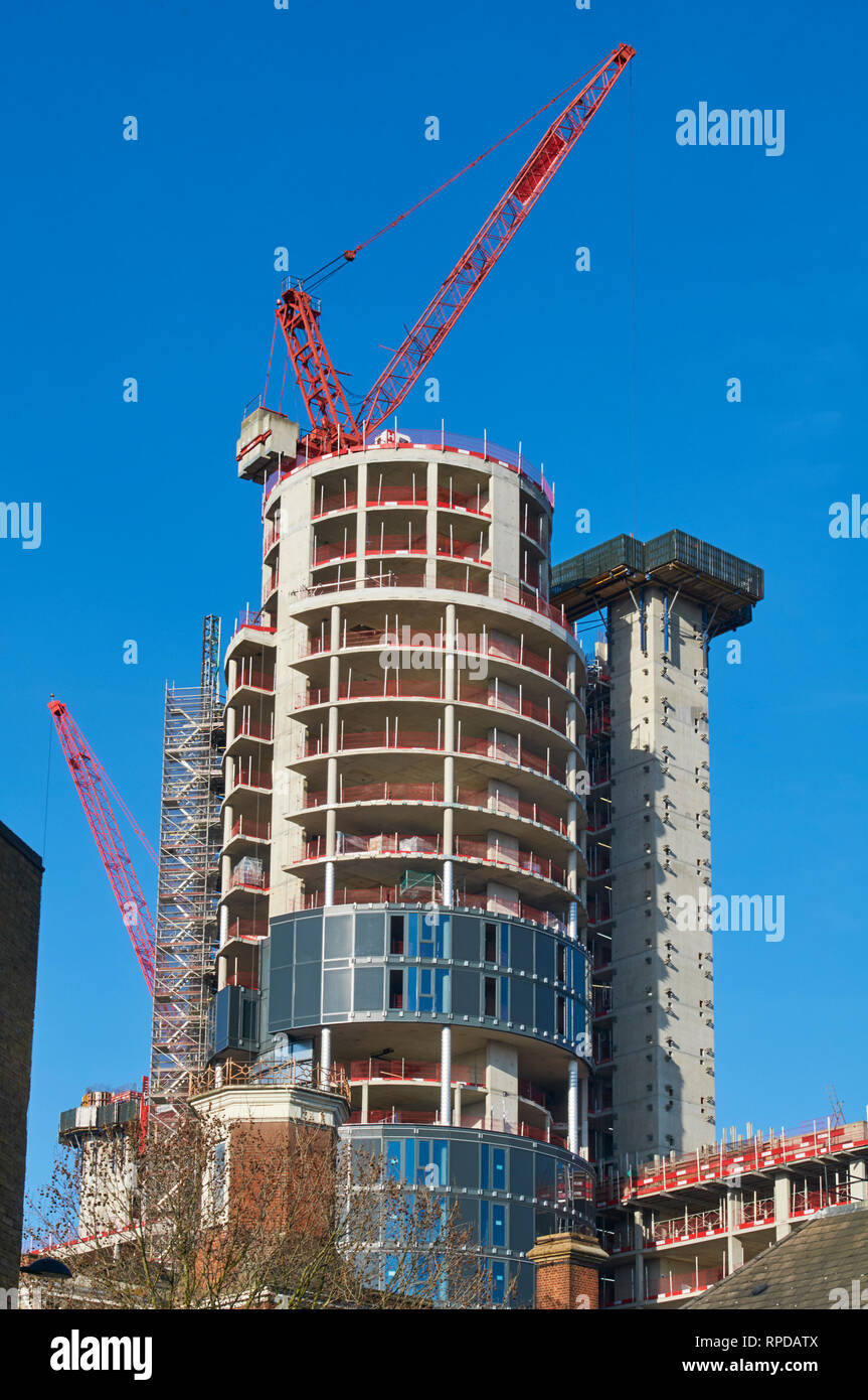 The main tower of the new City North residential development in Finsbury Park, London UK, under construction, with cranes - Stock Image
