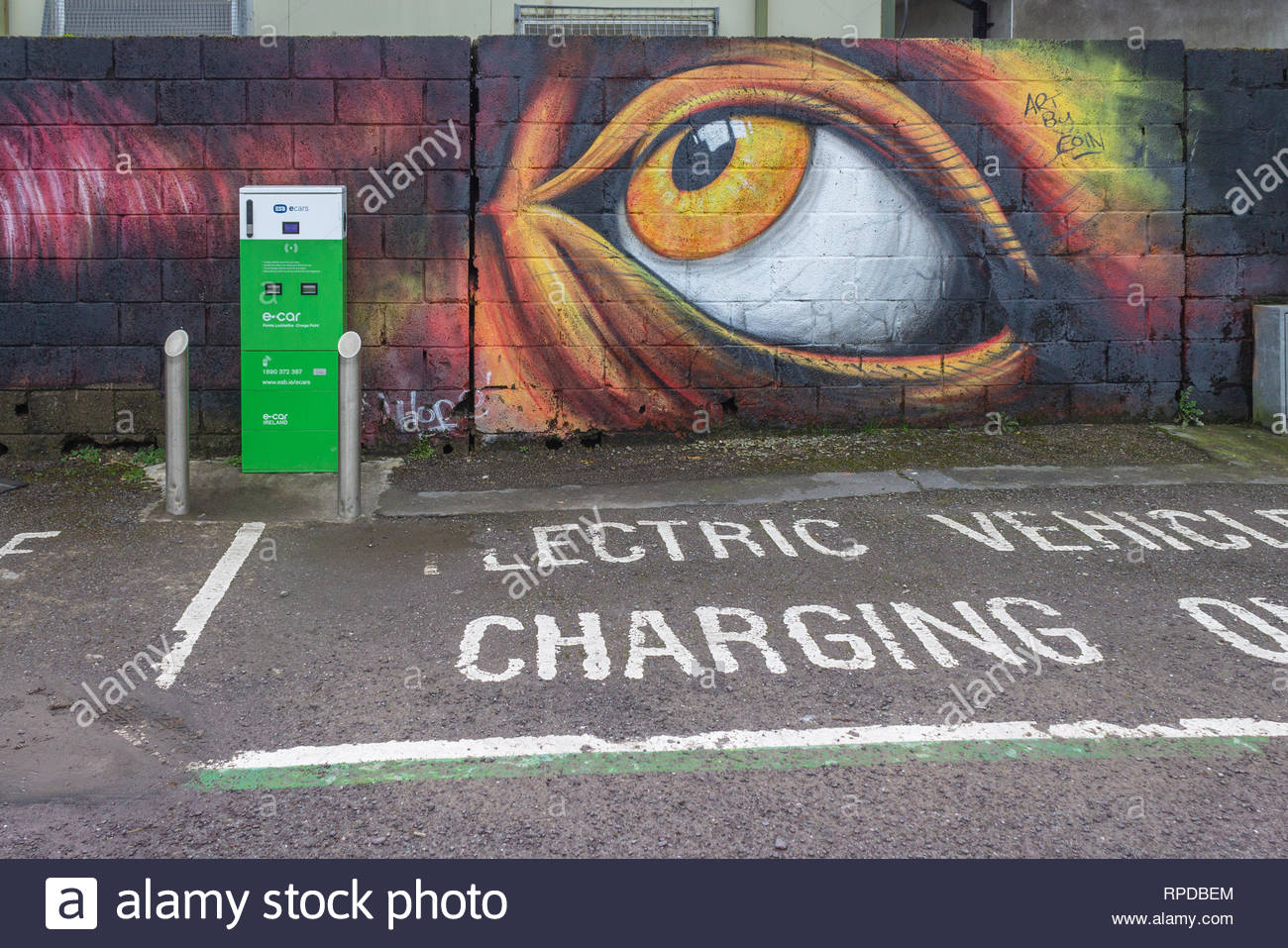 electric car charging point overlooked by a large painted eye - Stock Image