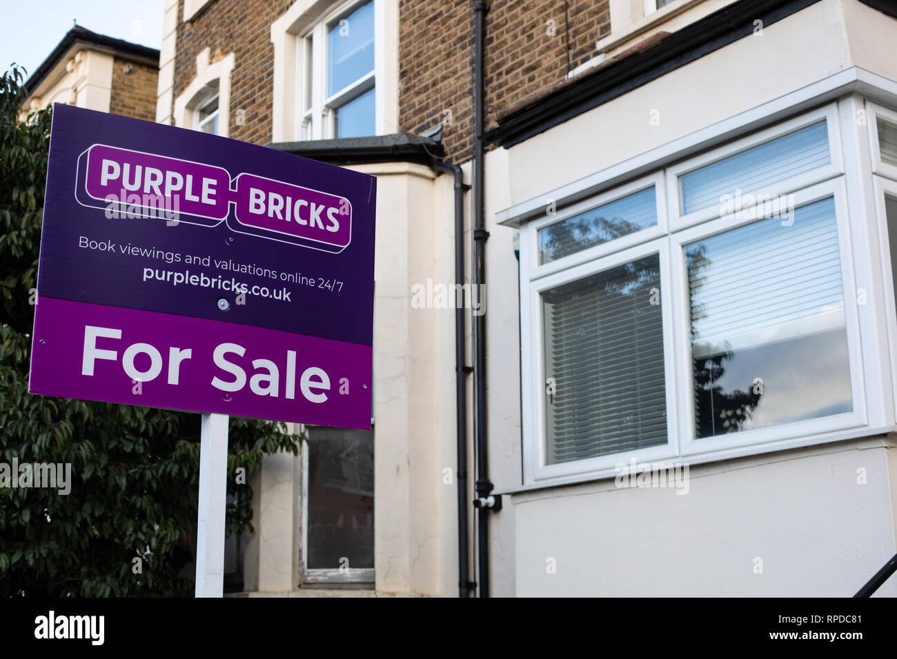 A Purple Bricks 'For Sale' sign outside a property in London - Stock Image