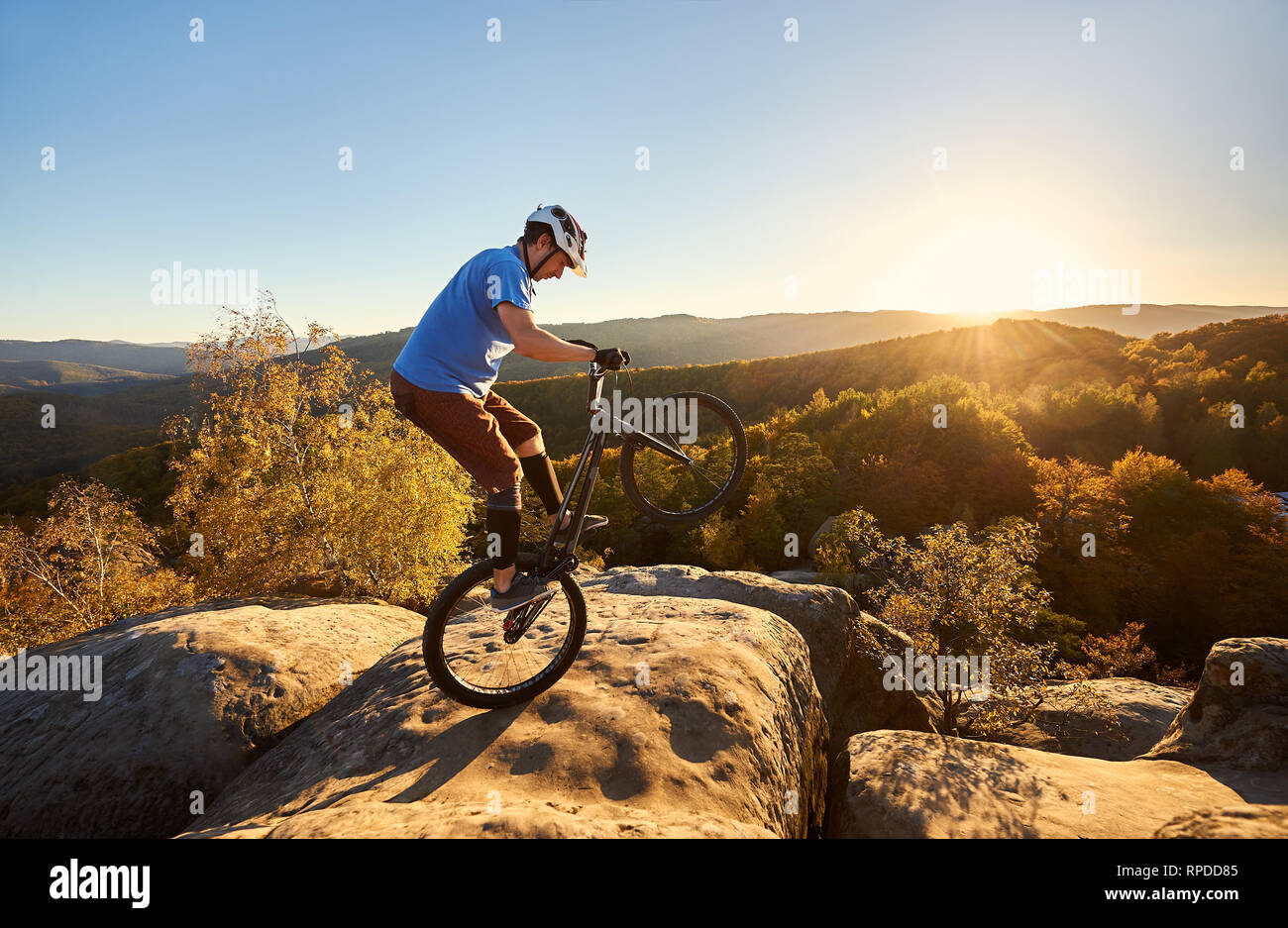 Professional cyclist riding on back wheel on trial bicycle. Sportsman rider balancing on the edge of big boulder on the top of mountain at sunset. Concept of extreme sport active lifestyle Stock Photo
