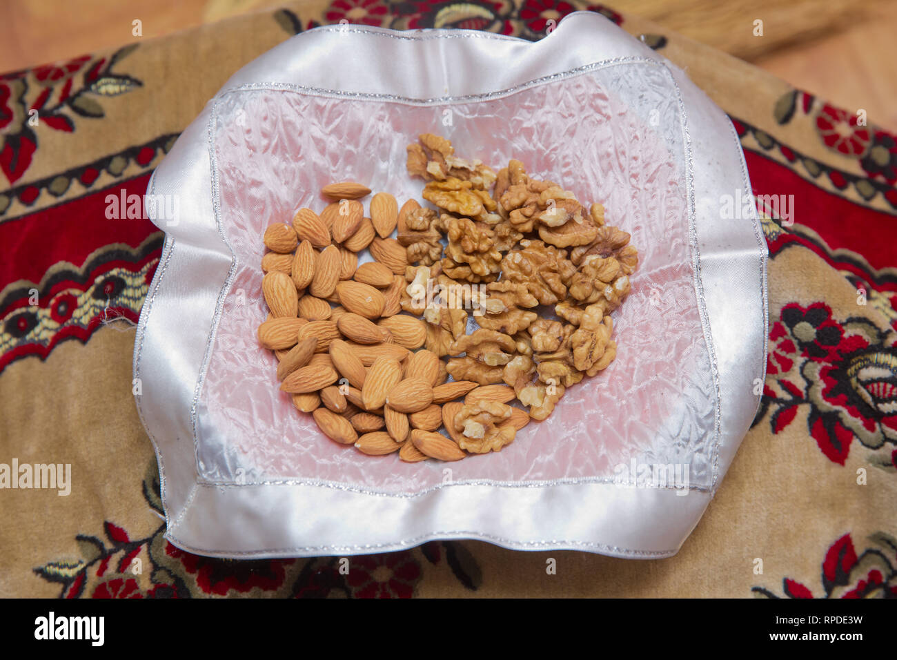 Cleaned almonds and walnuts inside the bowl . Assorted nuts on white, dry fruits, mix almond, walnuts - Stock Image