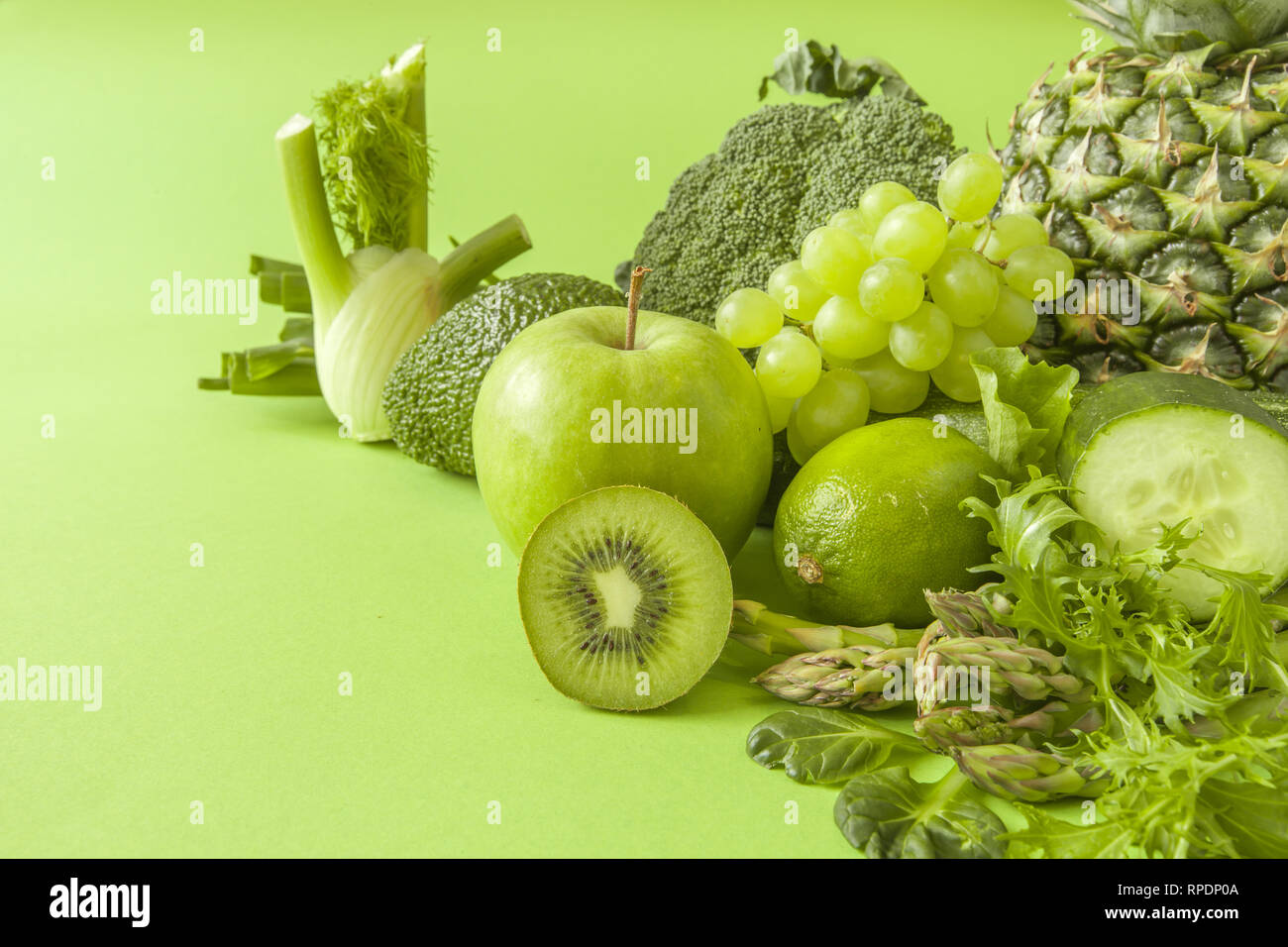 Green health smoothie fruits and vegetables, kale leaves, lime, apple, kiwi, grapes, banana, avocado, lettuce pineapple salat. Copy space. Raw, vegan Stock Photo