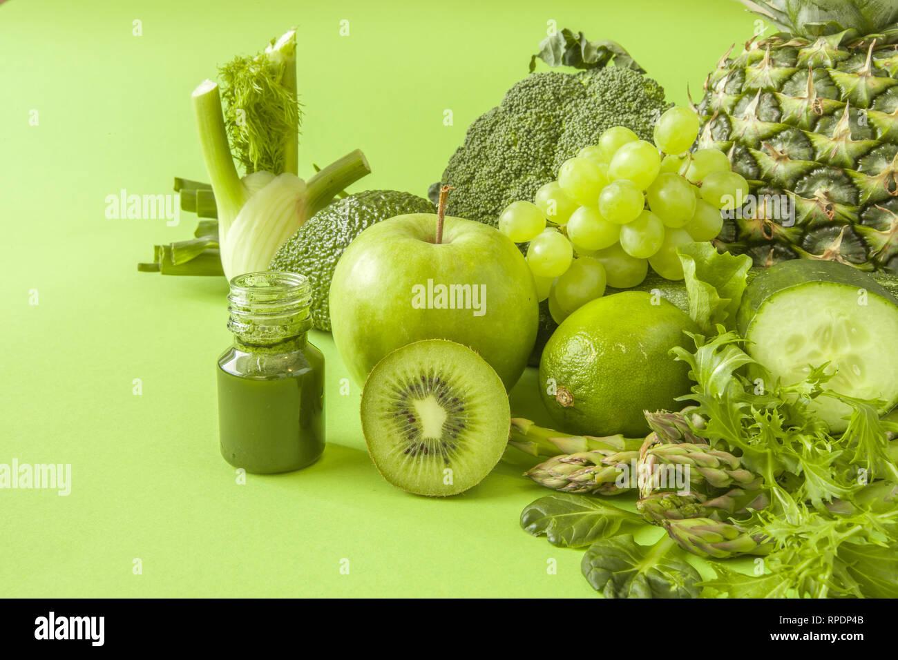 Green health smoothie fruits and vegetables, kale leaves, lime, apple, kiwi, grapes, banana, avocado, lettuce pineapple salat. Copy space. Raw, vegan Stock Photo