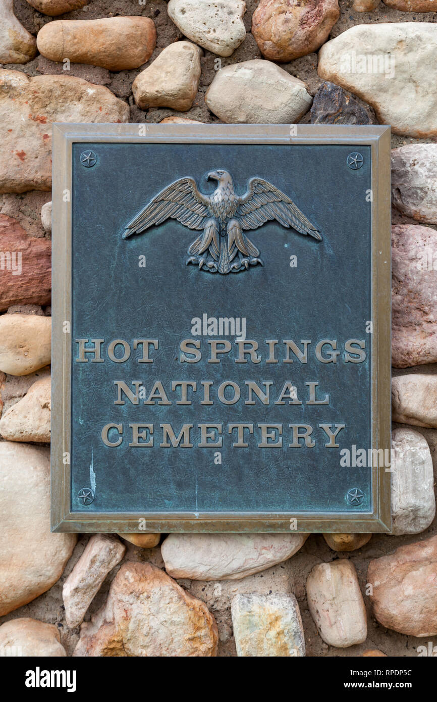 HOT SPRINGS, SOUTH DAKOTA - June 8, 2014:  A metal sign attached to a rock masonry wall marking the entrance to Hot Springs National Cemetery in Hot S - Stock Image