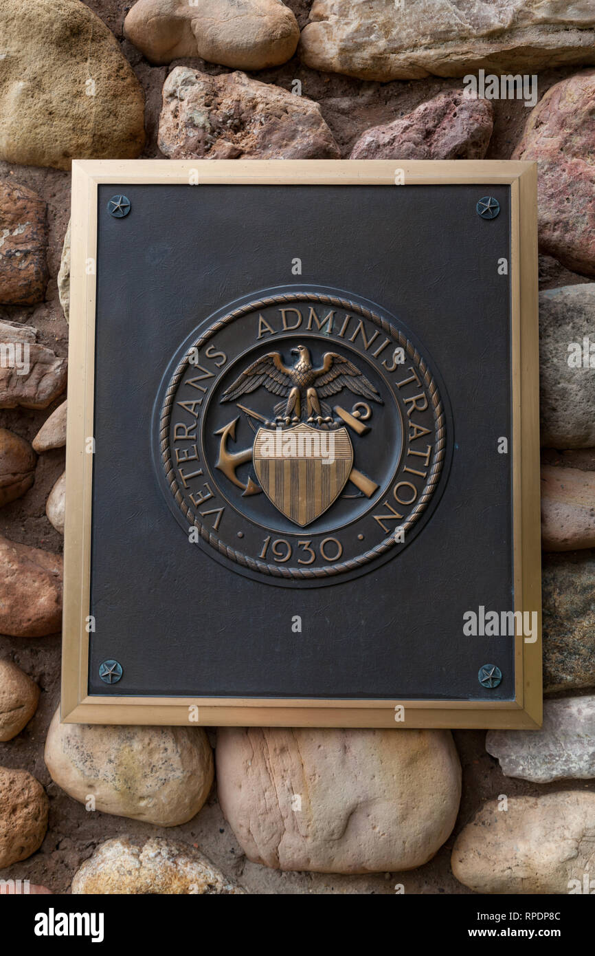 HOT SPRINGS, SOUTH DAKOTA - June 8, 2014:  A metal sign for the Veterans Administration attached to a rock masonry wall marking the entrance to Hot Sp - Stock Image