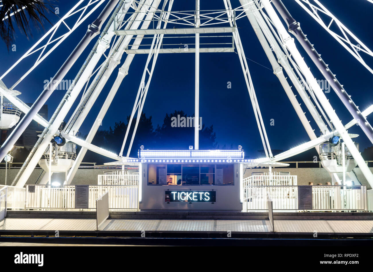 The big wheel at Bournemouth stands tall into the night sky and is brightly lit up white. - Stock Image
