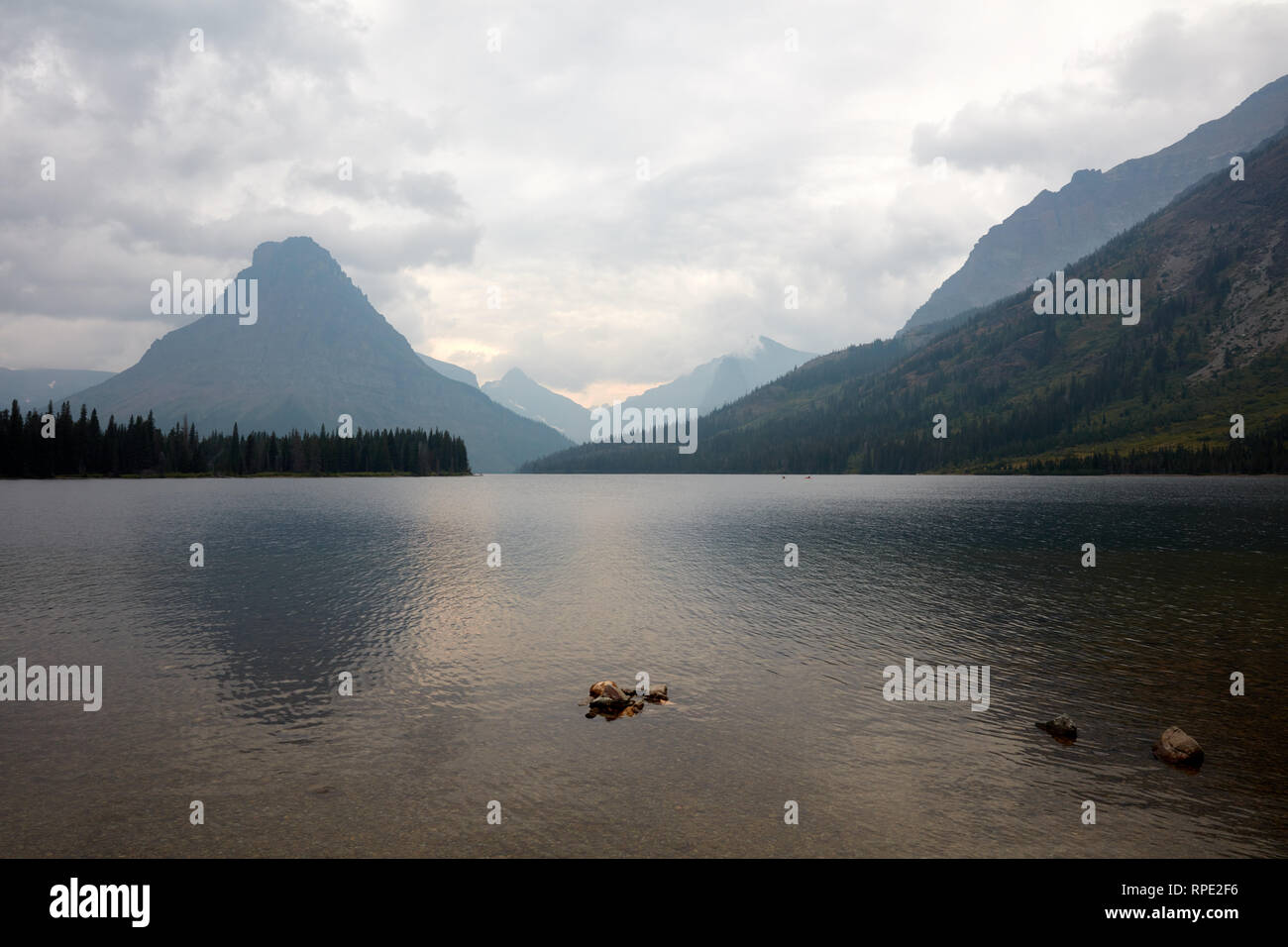 Two Medicine Lake in Glacier National Park in Montana with clouds and smoke from the Howe Ridge fire obscuring the view - Stock Image