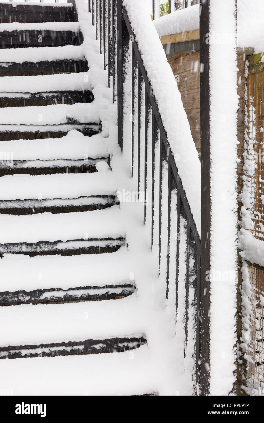 Exterior wooden stairway exposed to winter snow fall rendering access unsafe until cleared - Stock Image