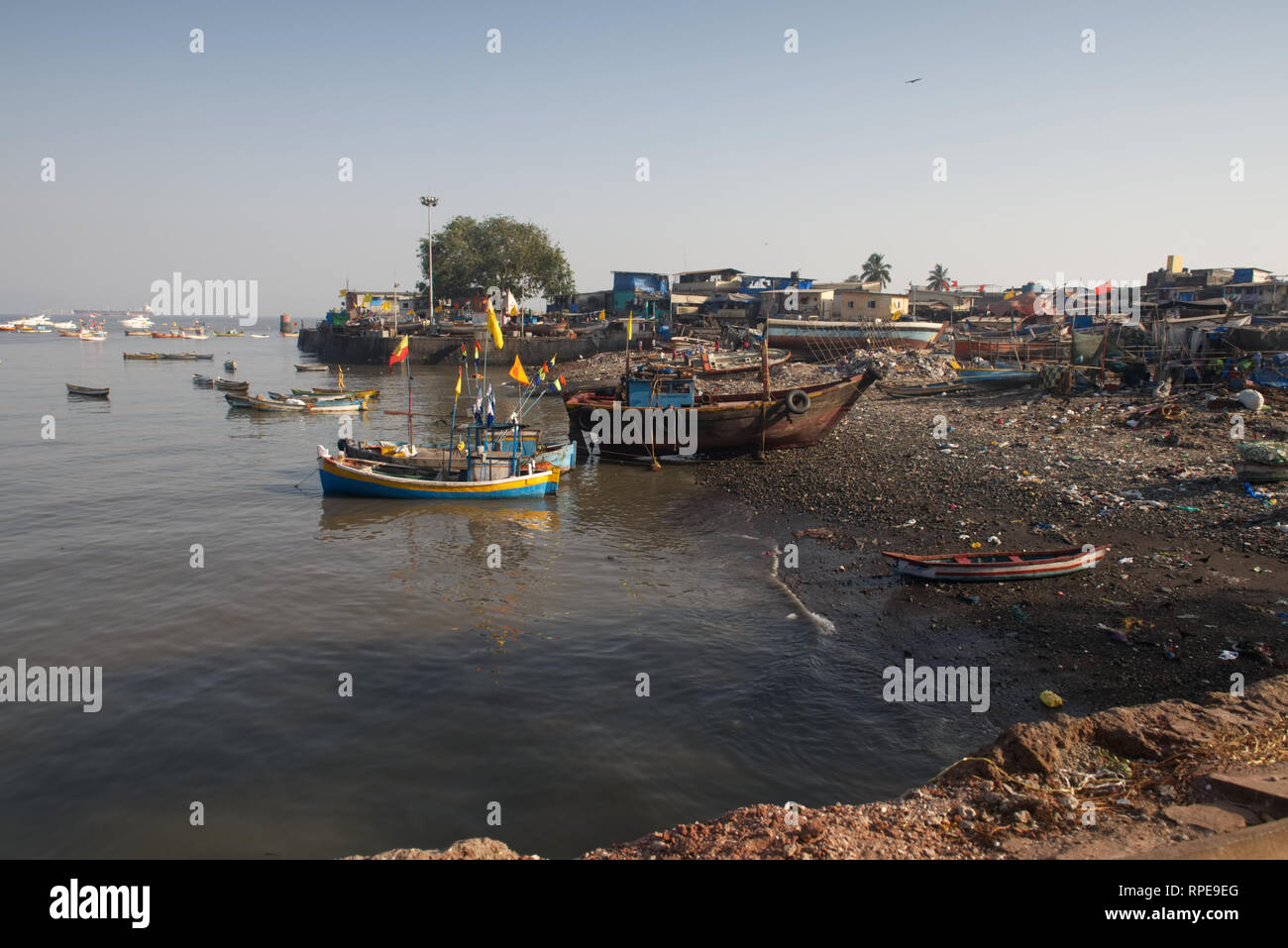 Marine littered beach adjacent Mumbai fishing village. Fisherfolk blame city development, pollution and over-fishing for the decline in fish stocks. - Stock Image