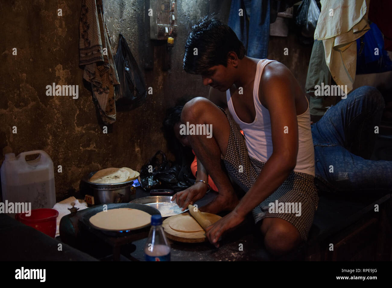 Traditional making of the staple food chapati is a timeless art. Here seen cooked for fellow workers in Dhobi Ghat, Mumbai - Stock Image