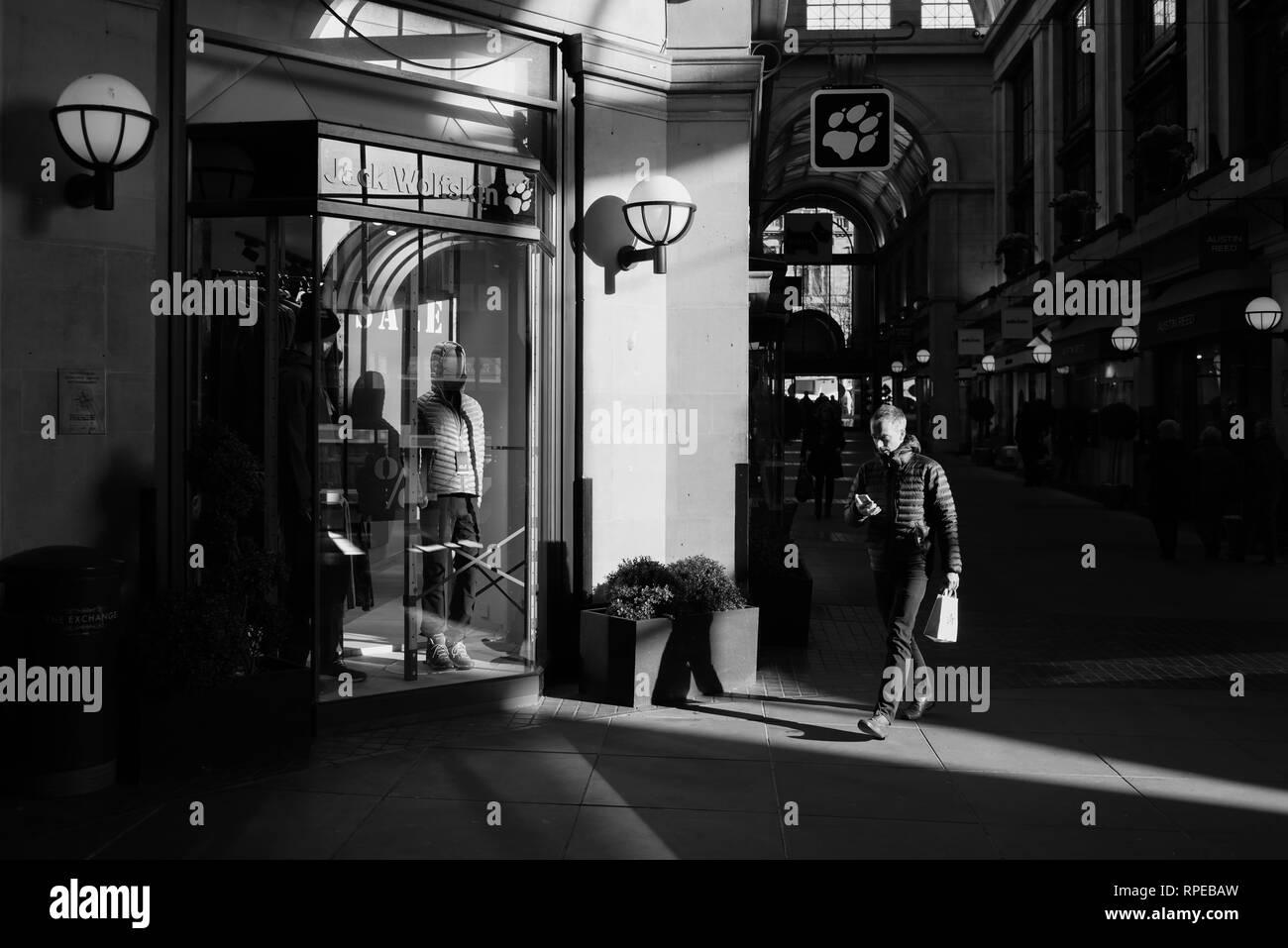 Man walking past Retail Stores in Urban Environment. - Stock Image