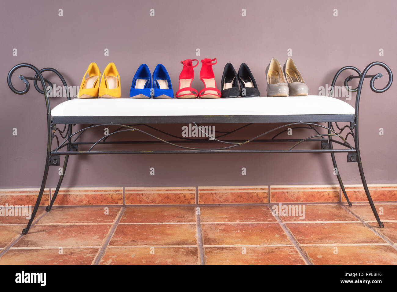 Collection of woman high heel shoes, on white sofa. - Stock Image