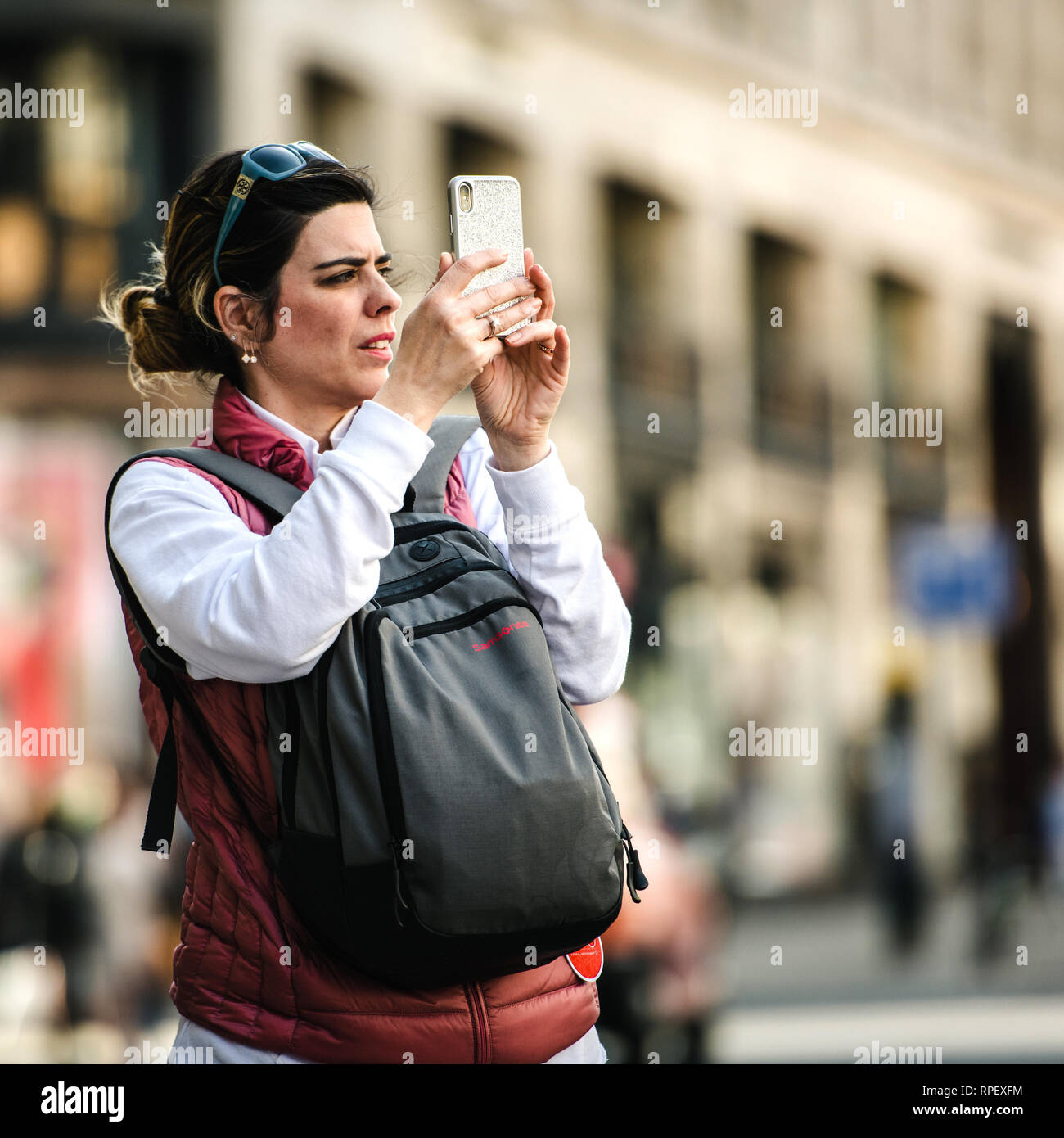 LONDON, UNITED KINGDOM - MAY 18, 2018: Woman taking photograph with her iPhone Xs smartphone on the fashionable Regent Street square image - Stock Image