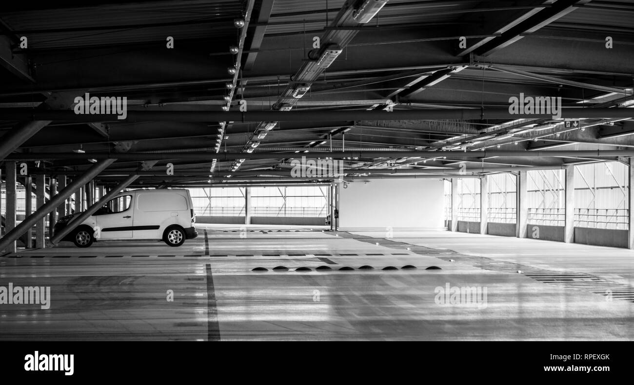 White van parked in modern airport parking - black and white wide image - Stock Image