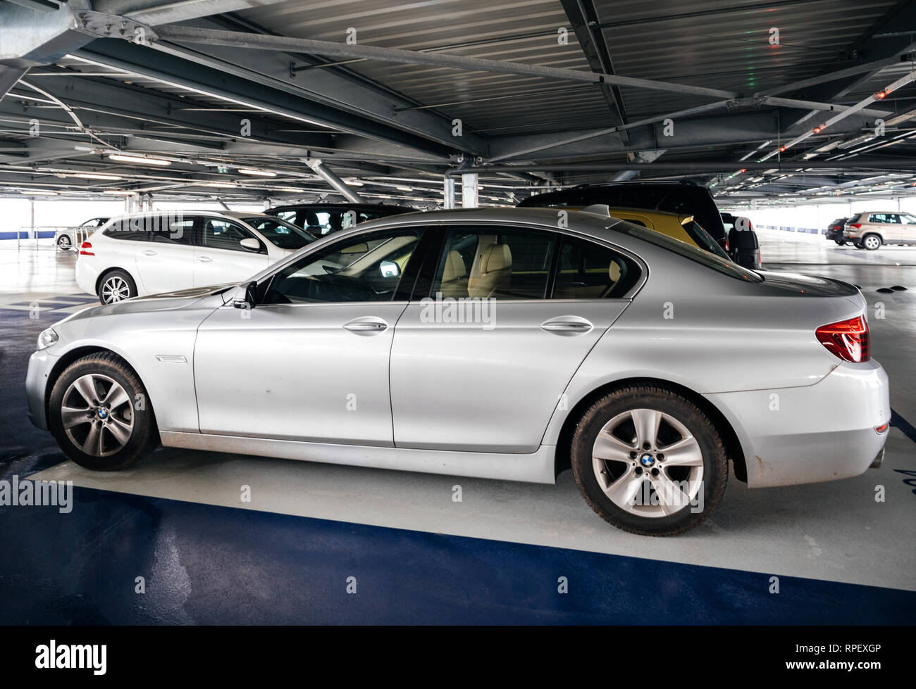 BASEL, SWITZERLAND - MAR 22, 2018: Luxury silver BMW parked inside modern Airport parking - Stock Image