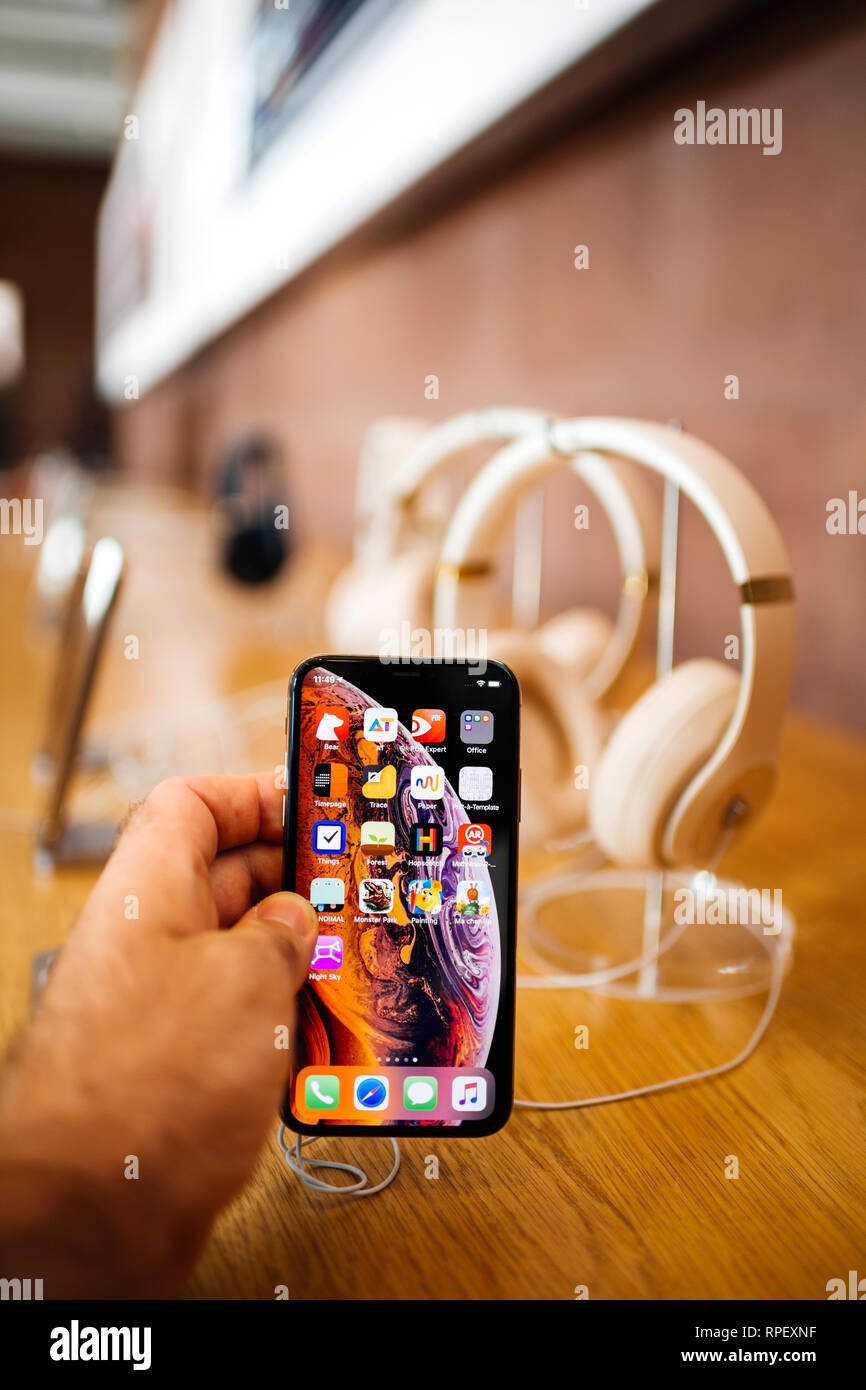a245df11082 PARIS, FRANCE - OCT 26, 2018: Man hand holding new iphone Xs Xr Max with  Apple Music app and multiple wireless bluetooth headphones Beats By Dr Dre  Studio 3 ...