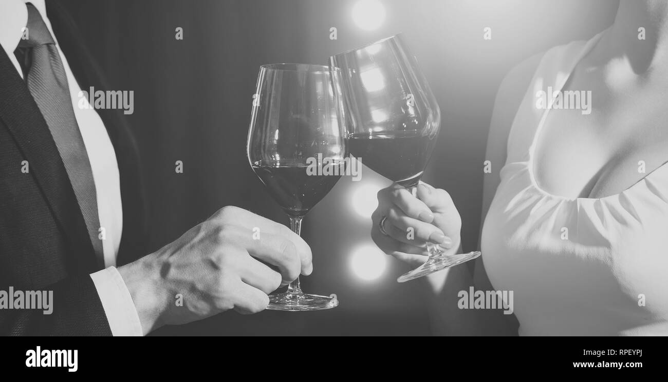 couple clink glasses with red wine at meeting or wedding - Stock Image