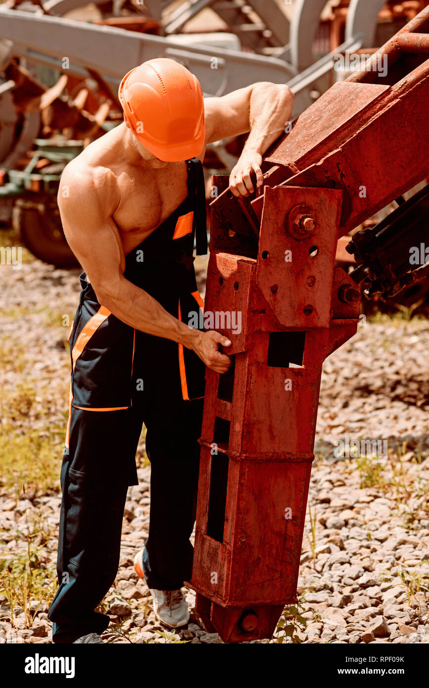 Repairman concept. Skillful repairman at work. Repairman fix heavy equipment. Machinery repairman in working uniform - Stock Image