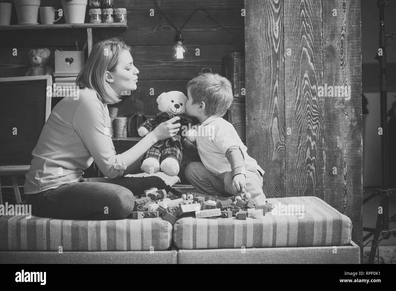Mother teaches son to be kind and friendly. Kindness and education concept. Family play with teddy bear at home. Mom and child play with soft toy - Stock Image
