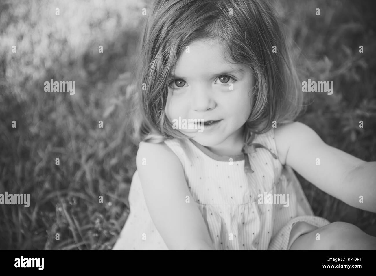 Baby girl with brown eyes on adorable face - Stock Image