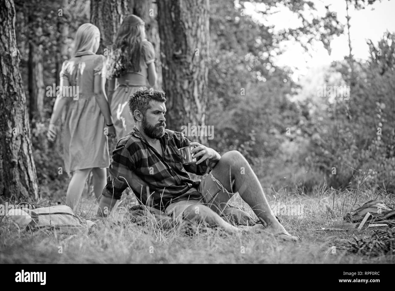 Bearded man drinking coffee or tea by campfire. Two girls in retro dresses walking on path in woods, turn back. Relaxation and tranquility concepts - Stock Image