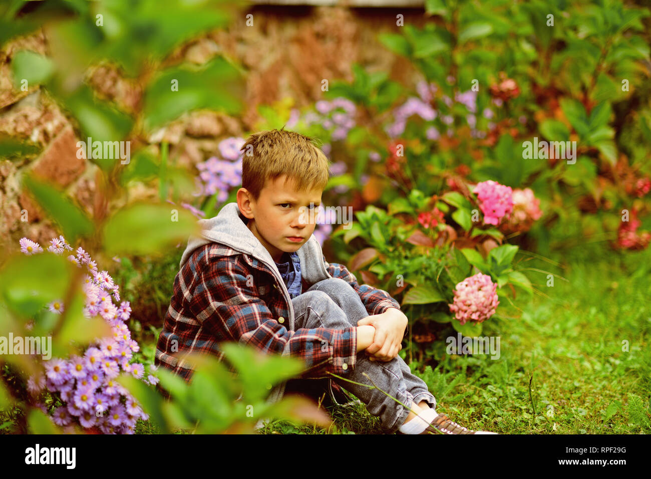 Small boy sit down under insult. Small boy feel deeply insulted. Child abuse and neglect. Insult by word or act. Engage in debate and not in insult - Stock Image