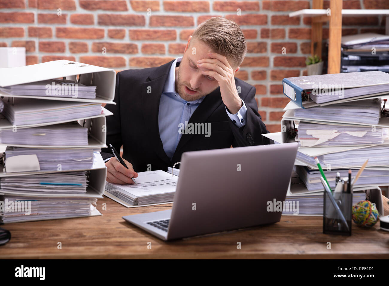 Stressful Businessman Sitting In Office With Stacked Of Files - Stock Image