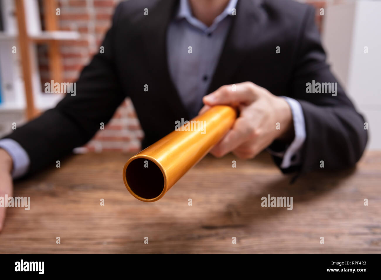 Mid-section Of A Person's Hand Holding Golden Relay Baton Over Wooden Desk - Stock Image