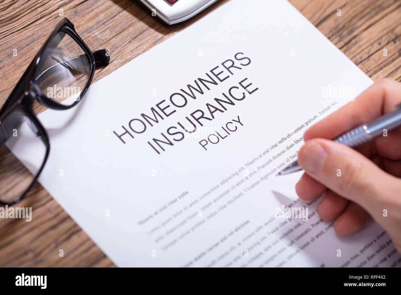 Overhead View Of A Person's Hand Filling Homeowners Insurance Policy Form Over Wooden Desk - Stock Image