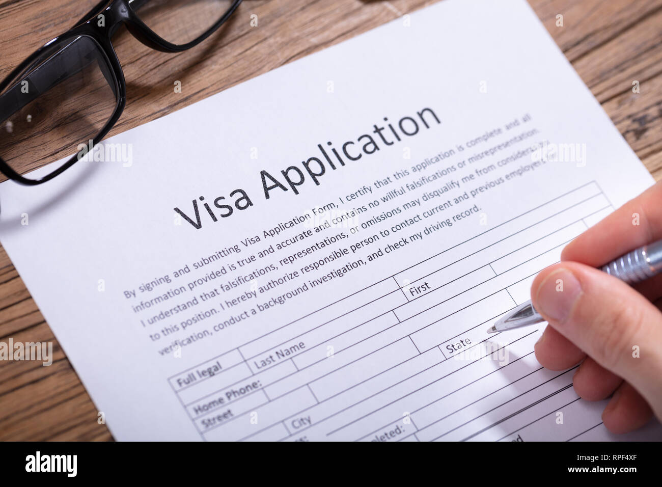 Close-up Of A Man's Hand Filling Visa Application Form With Pen Stock Photo