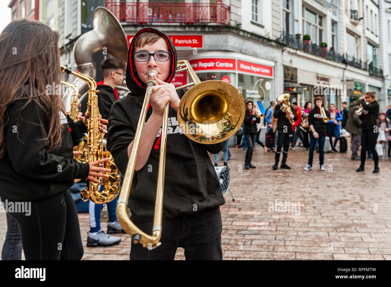 Cork, Ireland. 22nd Feb, 2019. Cork based brass band 'Rebel Brass' played in Cork city centre in front of huge crowds today. The band, made up of 12 to 18 year old young people, played on the Late Late Toy Show in November. Credit: Andy Gibson/Alamy Live News. - Stock Image