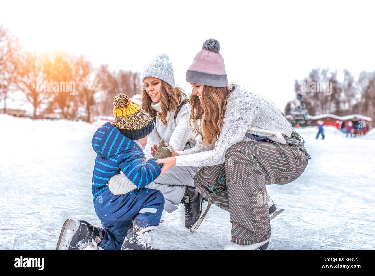 Young mother, two women, girlfriends raise son boy for 2-3 years, ice skating rink in winter city park. Concept first lesson on skating support, help - Stock Image