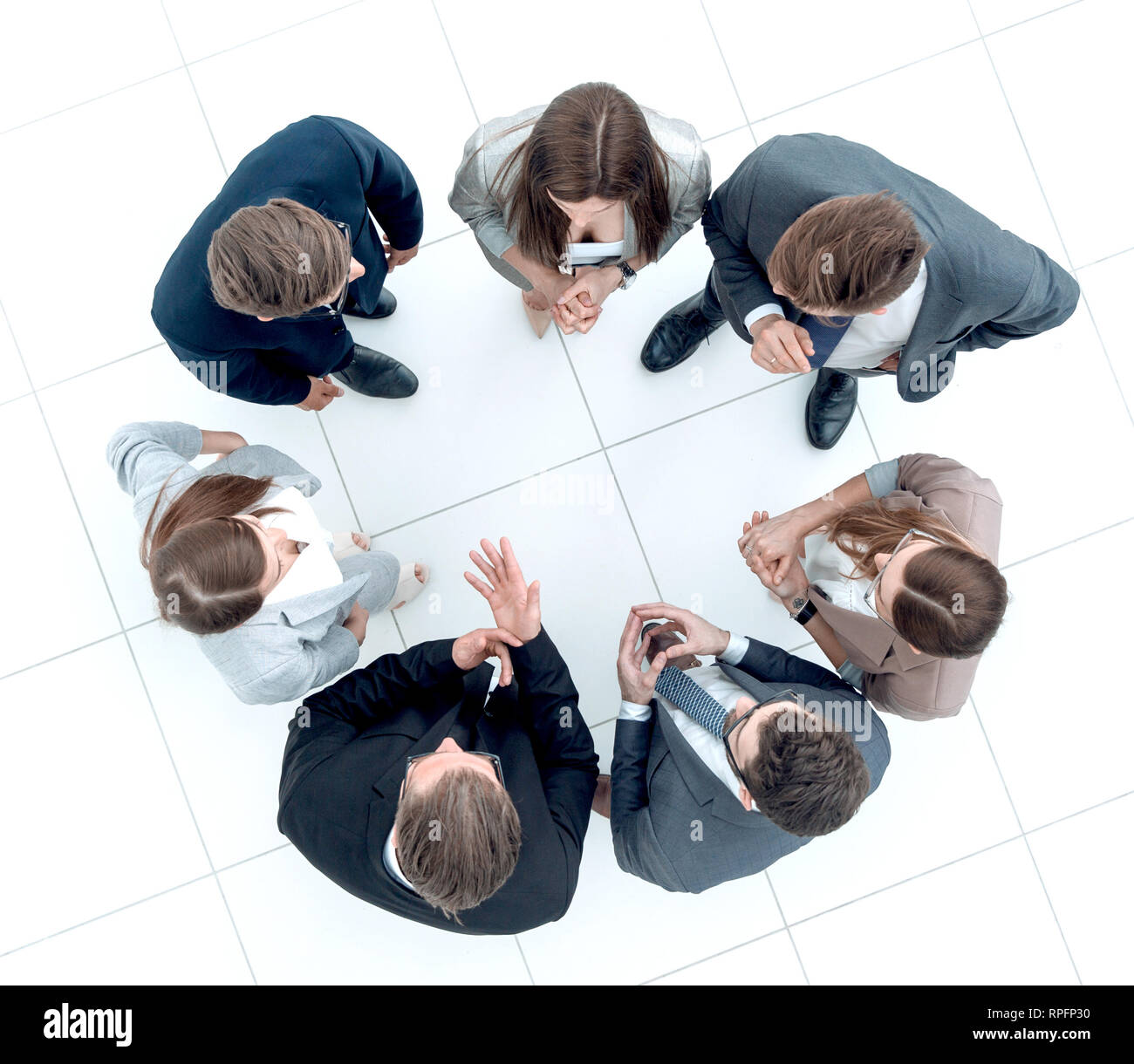 group of employees discussing something standing in a circle - Stock Image