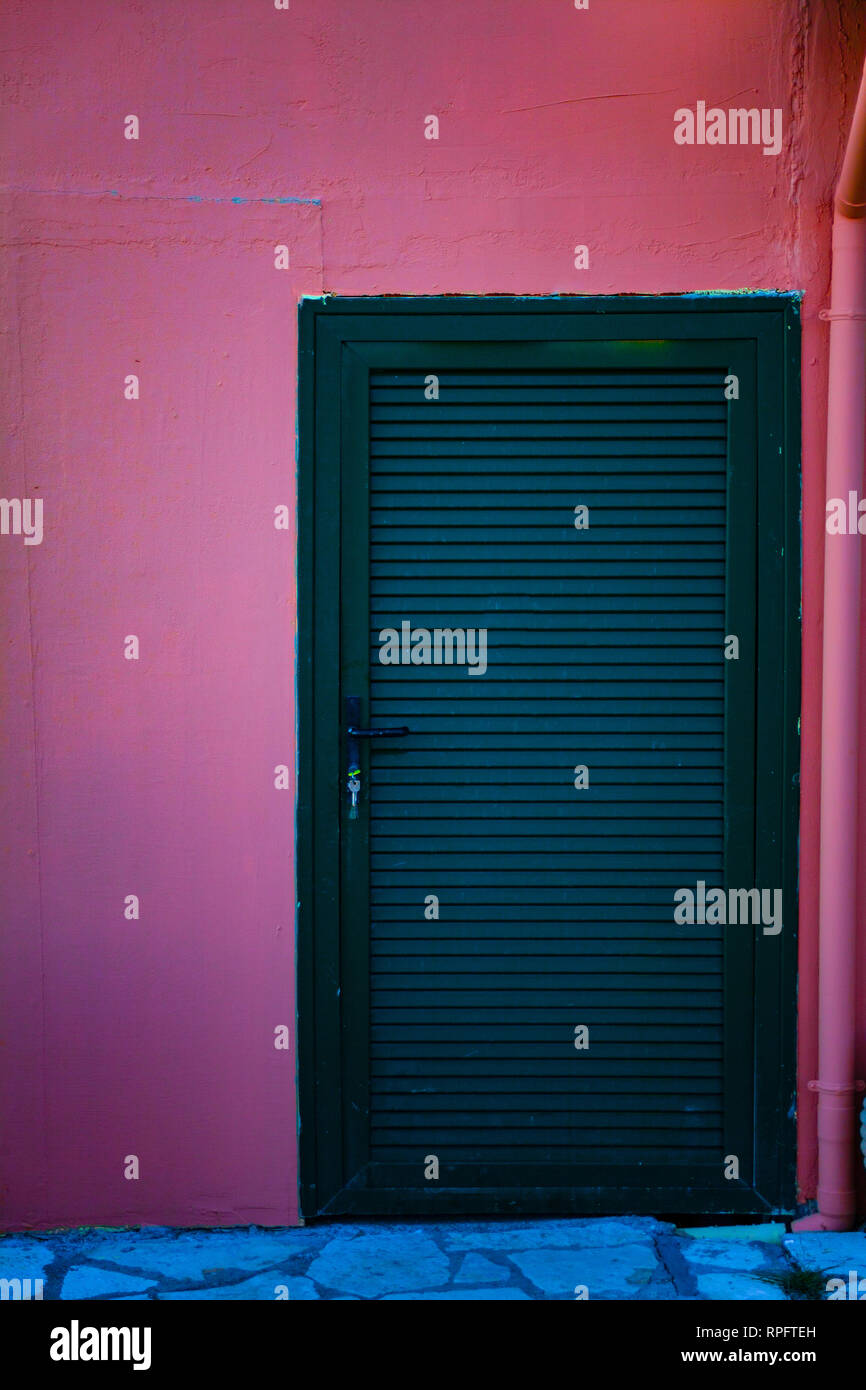 Green wooden doors to the room. Closed doors on the red wall. Copy space on the wall Stock Photo