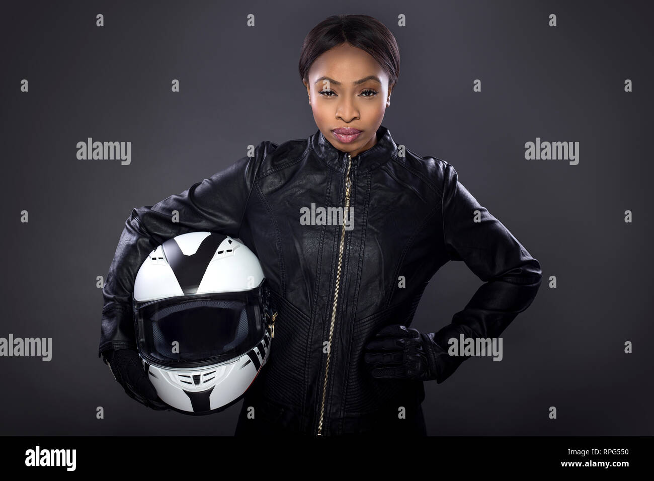 Black Female Motorcycle Biker Or Race Car Driver Or Stuntwoman Wearing Leather Racing Suit And Holding A Protective Helmet She Is Standing Confident Stock Photo Alamy